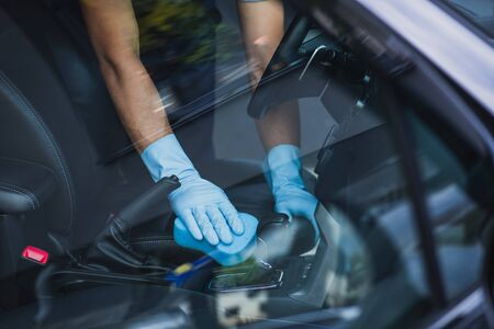 cropped view of car cleaner wiping car interior with sponge