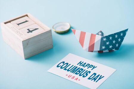 wooden calendar with October 14 date near paper boat with American flag pattern, compass and card with happy Columbus Day inscription on blue background Banque d'images - 132974032
