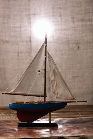 decorative ship with white sail on wooden surface