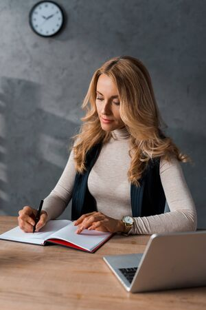 attractive businesswoman sitting at table and writing in notebook Stock Photo