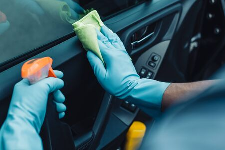 cropped view of car cleaner holding rag and spray bottle while cleaning car door