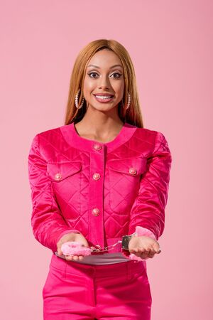 attractive, stylish african american woman in handcuffs looking at camera isolated on pink, fashion doll concept