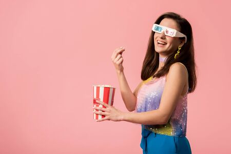 side view of happy young stylish disco girl in 3d glasses eating popcorn isolated on pink