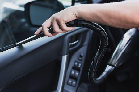 cropped view of car cleaner vacuuming car door