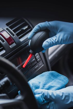 cropped view of car cleaner dusting dashboard with rubber air cleaner Stock Photo