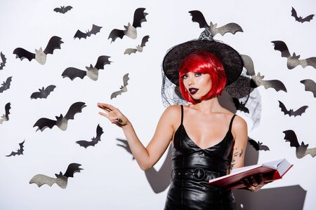 girl in black witch Halloween costume with red hair holding book near white wall with decorative bats