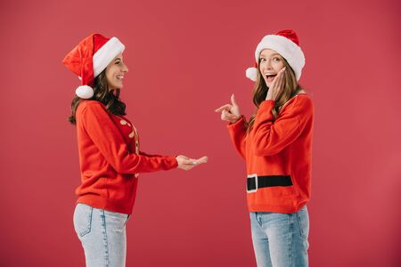 attractive and smiling woman in sweater and hat pointing with finger at hands of friend isolated on red