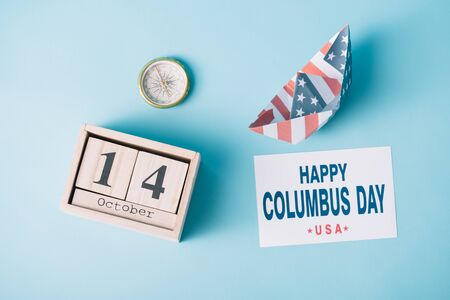 top view of calendar with October 14 date near paper boat with American flag pattern, compass and card with happy Columbus Day inscription on blue background Banque d'images - 132973572