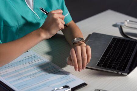vue recadrée d'une infirmière en uniforme assise à table et tenant un stylo pendant le quart de nuit Banque d'images