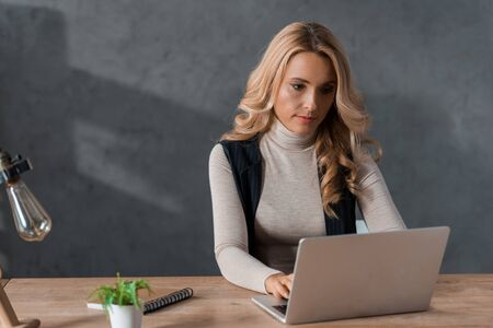 attractive and blonde businesswoman sitting at table and using laptop