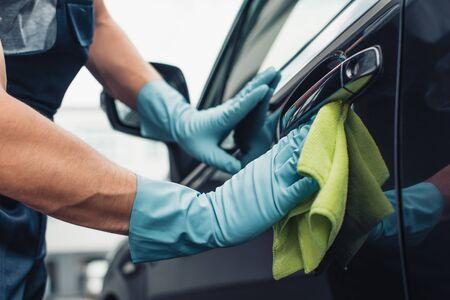 partial view of car cleaner wiping car door with rag Standard-Bild