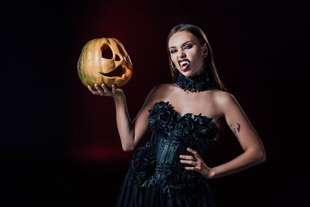 scary vampire girl with fangs in black gothic dress holding Halloween pumpkin on black background Banque d'images