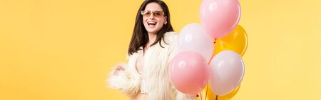 panoramic shot of happy party girl in faux fur jacket and sunglasses holding balloons isolated on yellow Foto de archivo