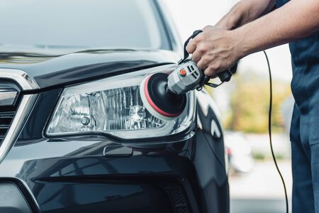 cropped view of car cleaner polishing headlamp with polish machine Archivio Fotografico