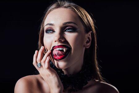 Fille vampire effrayante avec des crocs léchant les doigts isolés sur fond noir