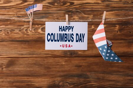 card with happy Columbus day inscription between American national flags and paper boat on wooden surface Banque d'images - 132998556