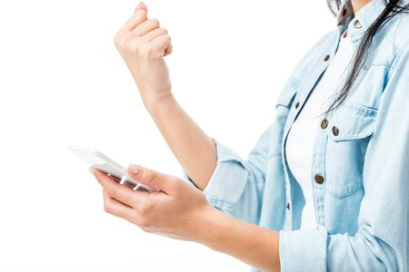 cropped view of woman in denim shirt showing yes gesture and holding smartphone isolated on white