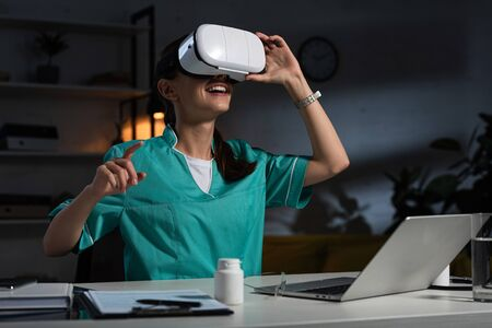 nurse in uniform with virtual reality headset pointing with finger during night shift Фото со стока