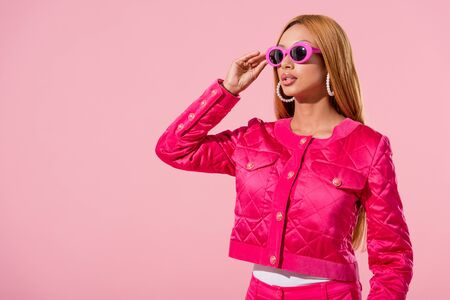 stylish african american woman in sunglasses looking away isolated on pink, fashion doll concept