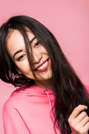 attractive asian woman in pink pullover smiling isolated on pink