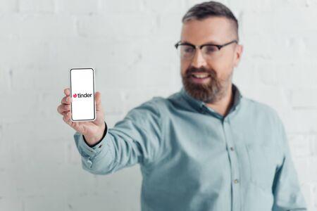 KYIV, UKRAINE - AUGUST 27, 2019: selective focus of handsome businessman holding smartphone with tinder logo