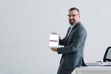 KYIV, UKRAINE - AUGUST 27, 2019: handsome businessman in formal wear holding digital tablet with tinder logo Editorial