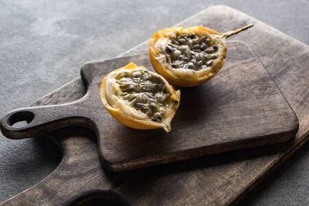 sweet granadilla on wooden cutting boards on grey background