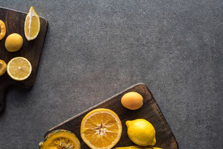 top view of yellow fruits and vegetables on wooden cutting boards on grey textured background with copy space 版權商用圖片