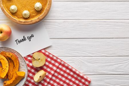 top view of pumpkin pie with thank you card on wooden white table with apples