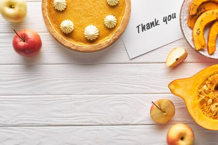 top view of delicious pumpkin pie with thank you card on wooden white table with apples