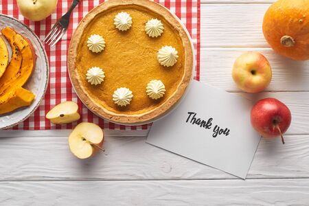top view of traditional pumpkin pie with thank you card on wooden white table with apples Reklamní fotografie
