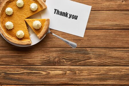 top view of tasty pumpkin pie and thank you card on wooden rustic table