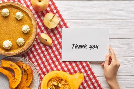 cropped view of woman holding thank you card near pumpkin pie on wooden white table with apples Reklamní fotografie
