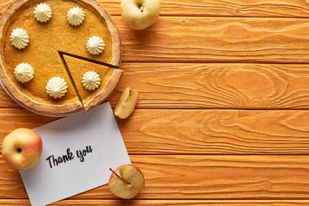 top view of pumpkin pie with thank you card on wooden table with apples