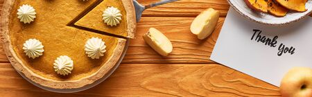 top view of pumpkin pie with thank you card on wooden table with apples, panoramic shot Reklamní fotografie