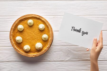 cropped view of woman holding thank you card near pumpkin pie on wooden white table Reklamní fotografie