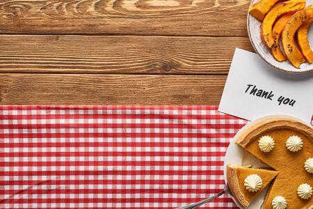 top view of tasty pumpkin pie and thank you card on wooden rustic table with checkered napkin