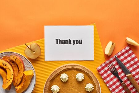 top view of delicious pumpkin pie with thank you card on orange background with apples Reklamní fotografie
