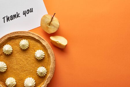 top view of pumpkin pie with thank you card on orange background with apples Reklamní fotografie