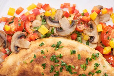 close up of homemade wrapped omelet with mushrooms and peppers