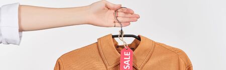 cropped view of woman holding elegant shirt with sale label isolated on white, panoramic shot
