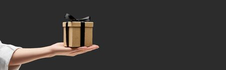 cropped view of woman holding gift box in hand isolated on black, panoramic shot Stockfoto