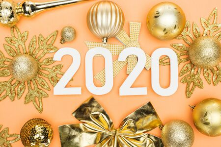 top view of white 2020 numbers on golden christmas decoration on orange background