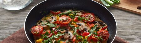 homemade omelet with vegetables and greens in frying pan on wooden table with ingredients