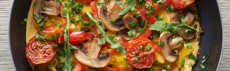 top view of homemade omelet with mushrooms, tomatoes and greens in frying pan Banco de Imagens