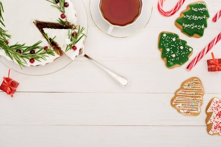 top view of christmas pie, cup of tea and christmas tree cookies on white wooden table