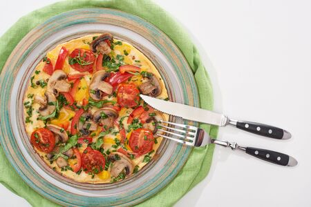 top view of plate with tasty omelet with tomatoes and mushrooms for breakfast on white table with napkin, fork and knife