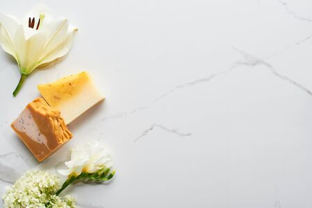 top view of natural soap pieces near fresh flowers on marble surface