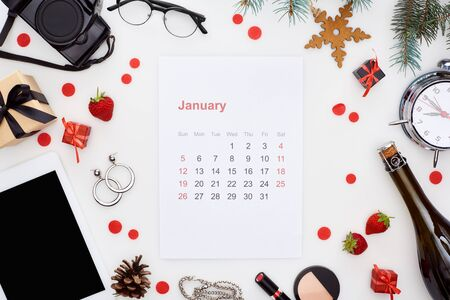january calendar page, digital camera, alarm clock, digital tablet, champagne bottle, cosmetics, glasses, fir branch, fresh strawberry, christmas baubles isolated on white 免版税图像