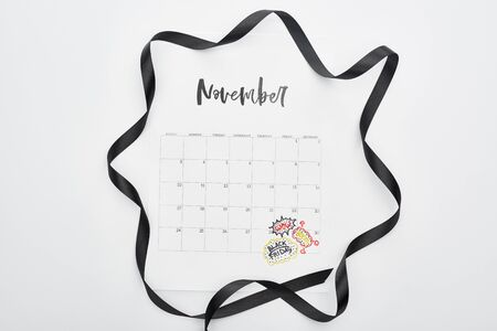 top view of calendar with November 29 marked date on white background with black ribbon